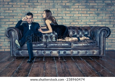 woman seduces a man on the leather couch - stock photo