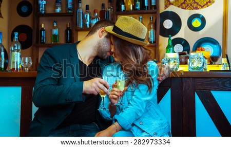 Woman seducing a man in a bar and drinking champagne. horizontal photo - stock photo