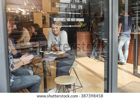 Woman seen through glass smiling while having coffee with friend - stock photo