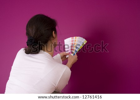 woman select a color to paint her wall (focus on the woman)