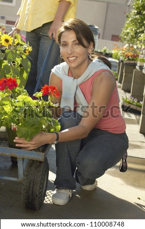 Woman selecting flower plant at botanical garden