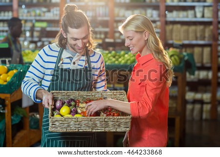 Woman selecting fresh vegetables from basket in supermarket