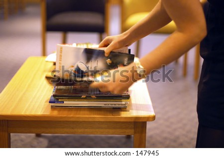 Woman selecting magazine in medical waiting room - stock photo