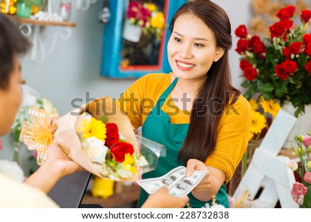 Woman selling flowers to a man - stock photo
