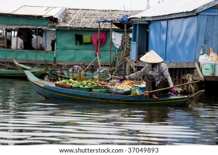 woman selling fruits on a boat in a fishing village in cambodia - stock photo