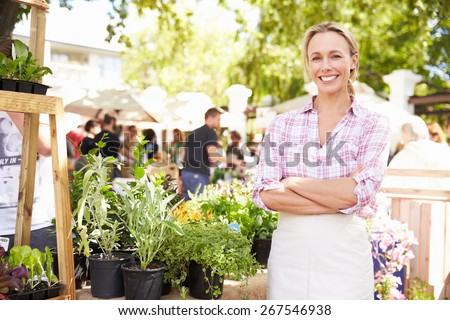 Woman Selling Herbs And Plants At Farmers Food Market - stock photo