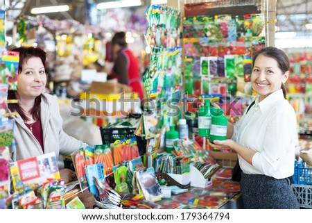 woman selling liquid fertilizer to mature buyer in store for gardeners - stock photo