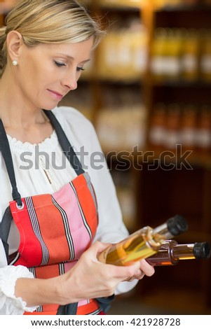 woman selling oil in grocery store - stock photo
