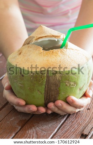 woman serve a tropical coconut cocktail with a straw - stock photo