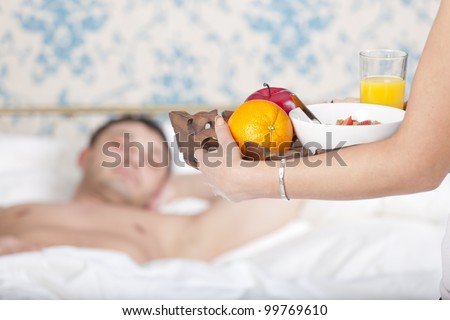 woman serving breakfast for man to bed at home - stock photo