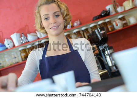 woman serving coffees at the cafe counter