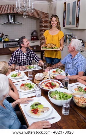 Woman serving food to her family in the kitchen at home - stock photo