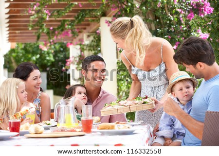 Woman Serving Meal To Two Families - stock photo