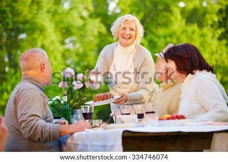 Woman serving ring cake at birthday party with senior people in a garden - stock photo