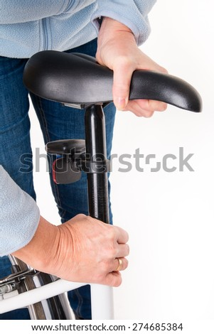 Woman sets height of  bicycle saddle before cycling - studio shoot