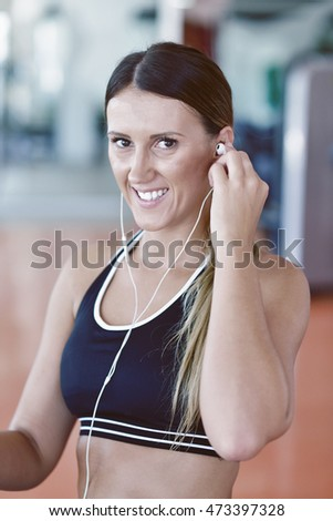 woman setting music on smart phone putting earphones before exercise