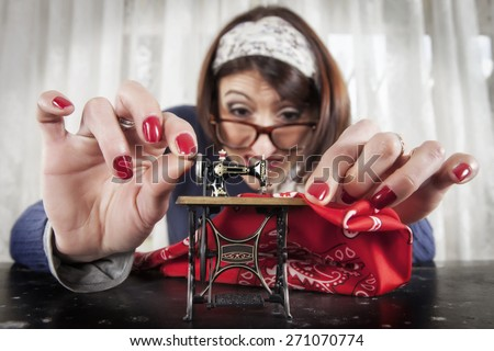 Woman sewing with a small sewing machine, humorous photography - stock photo