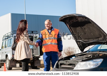 Woman shaking hands with mechanic car breakdown crash accident man - stock photo