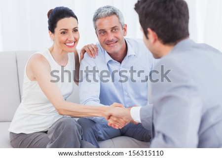 Woman shaking hands with salesman sitting beside husband on couch at home - stock photo