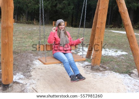 Woman shaking on a swing in the park in the fall