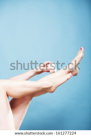 woman shaving her legs with electric shaver depilation on blue. Beauty and body skin care concept. - stock photo