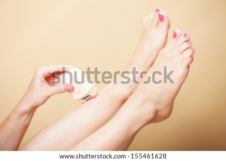 woman shaving her legs with electric shaver depilation on orange. Beauty and skin body care concept. - stock photo