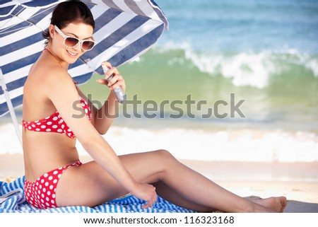 Woman Sheltering From Sun Under Beach Umbrella Putting On Sun Cream - stock photo