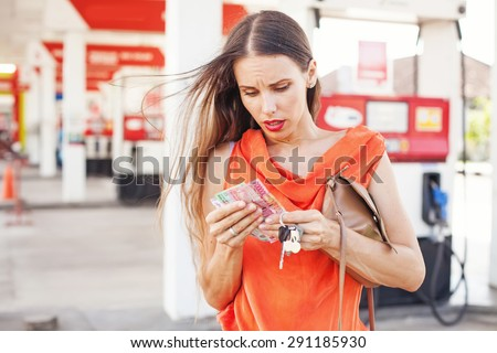 woman shocked by the price of a fuel - stock photo