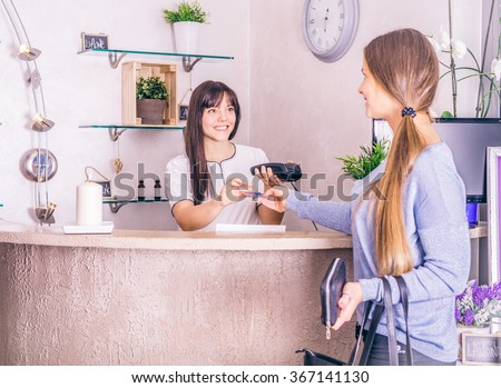 Woman shopping and paying with credit card in a shop - Customer paying with card for her purchase - stock photo