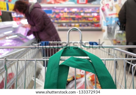 Woman shopping at the supermarket with trolley - stock photo
