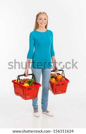 Woman shopping. Cheerful young woman carrying shopping bags full of goods and smiling while isolated on white
