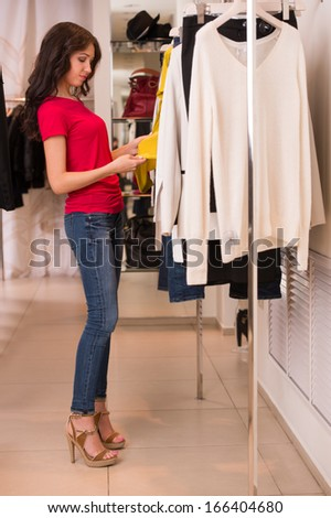 Woman shopping choosing dresses. Beautiful young shopper in clothing store. Full length - stock photo