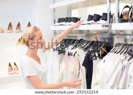 Woman shopping clothes and shoes. Shopper looking at clothing indoors in store. Beautiful blonde caucasian female model wearing fashion sunglasses. Focus on model. - stock photo