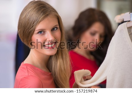 Woman shopping clothes. Shopper looking at camera indoors in store. Beautiful happy smiling caucasian female model. - stock photo