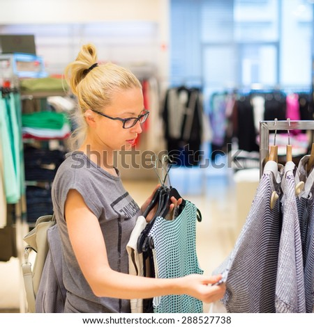 Woman shopping clothes. Shopper looking at clothing indoors in store. Beautiful blonde caucasian female model wearing black glases. Focus on model. - stock photo