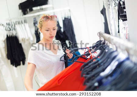 Woman shopping clothes. Shopper looking at clothing indoors in store. Beautiful blonde caucasian female model wearing fashion sunglasses. Focus on model. - stock photo