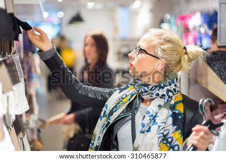 Woman shopping clothes. Shopper looking at clothing indoors in store. Beautiful blonde caucasian female model wearing black glasses, casual black leather jacket an colorful scarf.