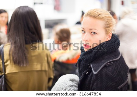 Woman shopping clothes. Shopper queuing in line at cashier in textile store. Beautiful blonde caucasian female model.  - stock photo