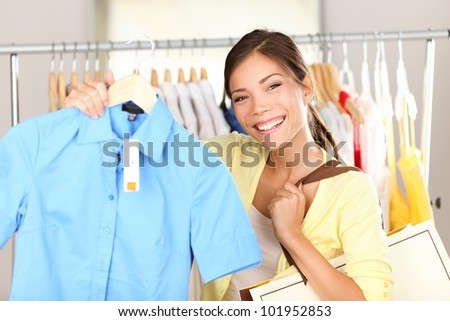 Woman shopping clothes showing shirt in clothing store smiling happy looking at camera. Beautiful young mixed race Asian Chinese / Caucasian young woman shopper.