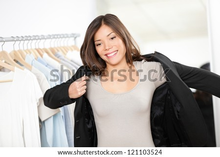 Woman shopping for business suit clothes in clothing store trying jacket for businesswoman. Beautiful young professional business woman of mixed Asian Chinese / Caucasian ethnicity looking in mirror - stock photo