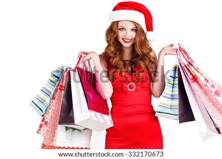 Woman shopping for christmas gifts. Young caucasian girl smiling with shopping bags and santa hat. Copy space on the side. appy shopping Christmas woman with bags white background