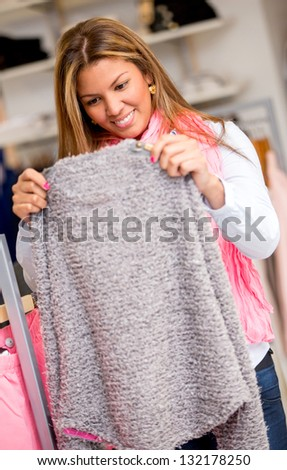 Woman shopping for clothes at a retail store - stock photo