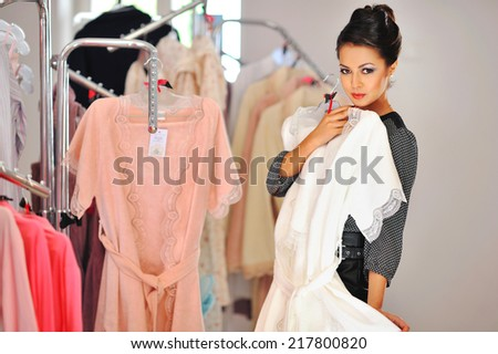 Woman shopping for dress in clothing retail store - stock photo