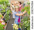 Woman shopping for flowers in garden centre  variation of plants - stock photo