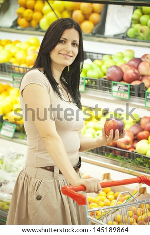 Woman shopping for groceries holding an apple - stock photo