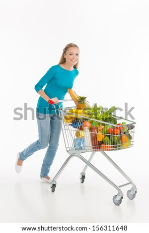 Woman shopping. Full length of cheerful young woman carrying shopping cart full of goods and smiling while isolated on white - stock photo