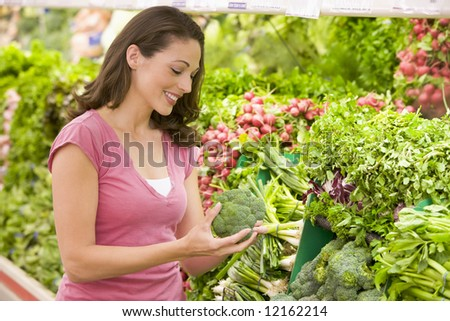 Woman shopping in produce section of supermarket - stock photo