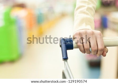 Woman shopping in super market and pushing cart hand closeup - stock photo