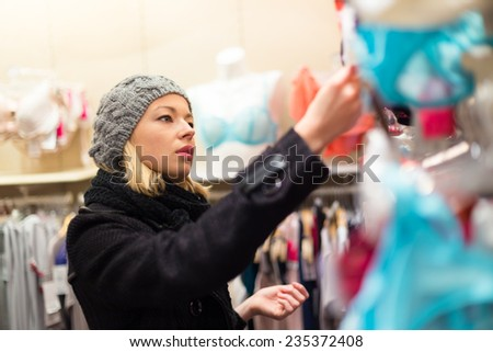 Woman shopping lingerie . Shopper looking and choosing clothing indoors in store. Beautiful blonde caucasian female model wearing winter coat and fashionable knitted cap. - stock photo