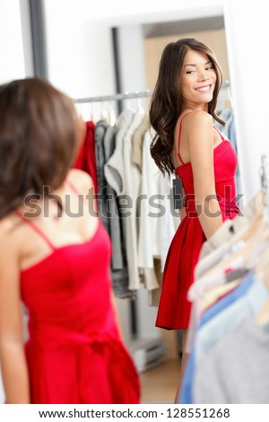 Woman shopping looking in mirror trying clothes dress in clothing store. Young beautiful multicultural woman trying on red dress in fitting room. Mixed race Caucasian Asian girl in her twenties. - stock photo